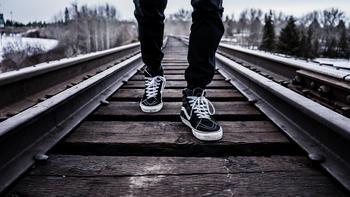 Mann som går på togskinner